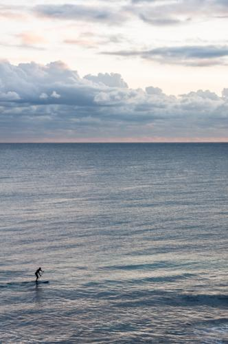 Person Riding on Stand up Paddleboard with Ocean and Horizon