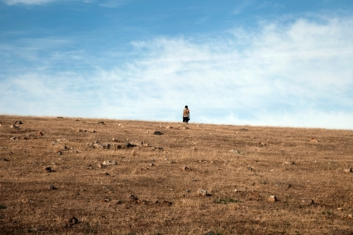 Person standing alone on a hill