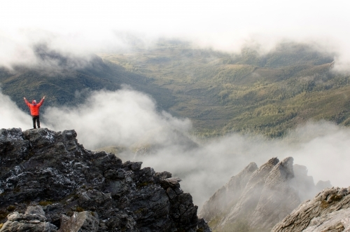 Person standing on a cliff in a misty mountain range
