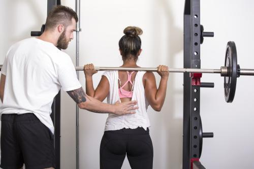 Personal trainer instructs client in squat technique