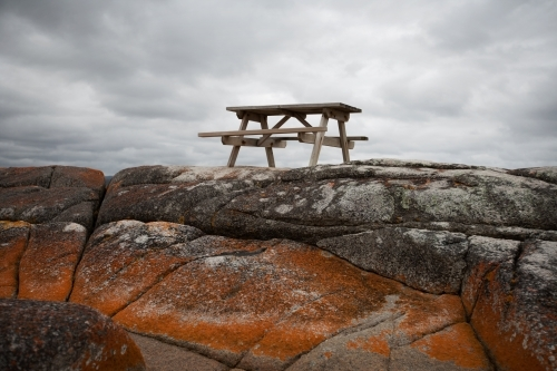 picnic table situated on lichen covered rocks