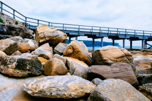 Piled up boulders and rocks with textures and bridge in the background