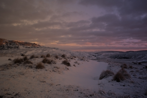 Pink sunrise over snow covered hills