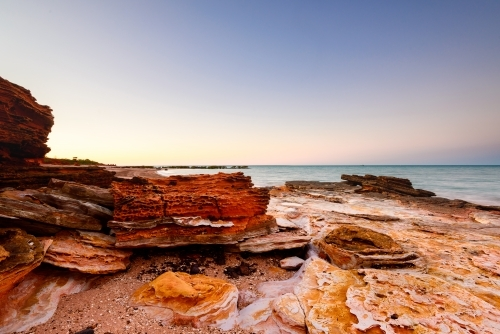 Pink sunset lighting on patterned rocky beach and bay