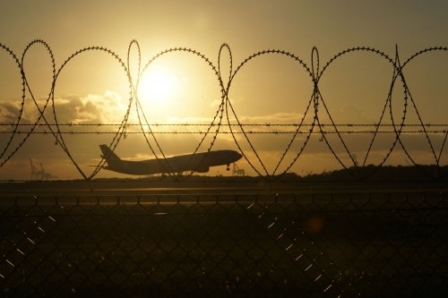 Plane landing at sunrise through security fence