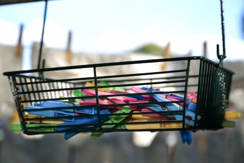Plastic pegs in a wire basket.