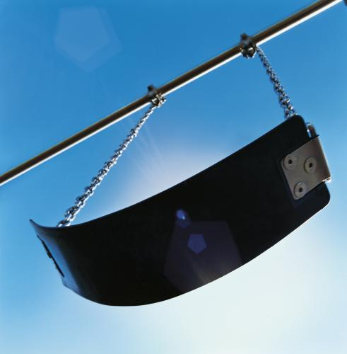 Playground swing from below with sun and blue sky behind