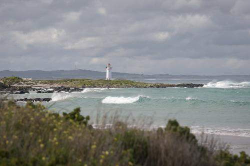 Griffiths Island coast with distant white Lighthouse at Port Fairy