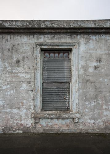 Abandoned grey building and shuttered window