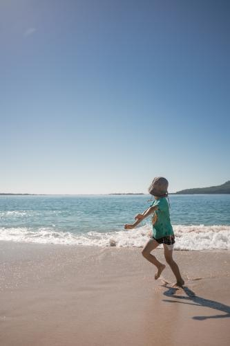 Cute 6 year old boy plays happily in the water on a Port Stephens beach