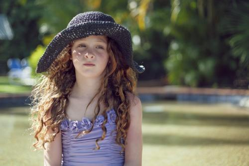 Portait of girl wearing a sunhat in Summer