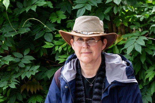 Portrait of a female tourist wearing an Australian hat, glasses and rain jacket with greenery behind