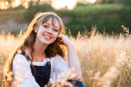 Portrait of a happy smiling young woman at sunset in fluffy grass
