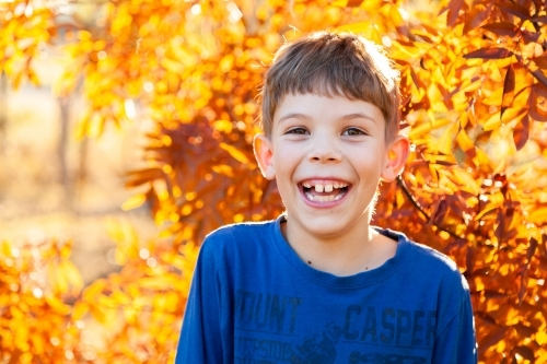 Portrait of a happy young boy laughing in autumn