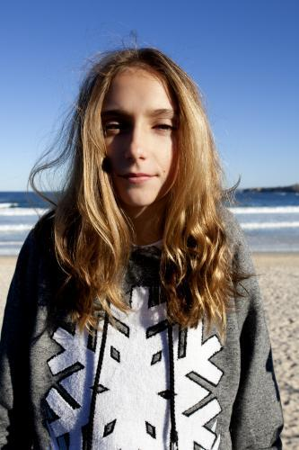 Portrait of a sunlit pre teen girl at the beach in winter
