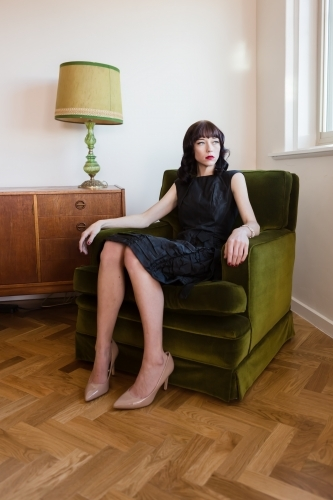 Portrait of a woman in a beautiful dress sitting in a green velvet armchair