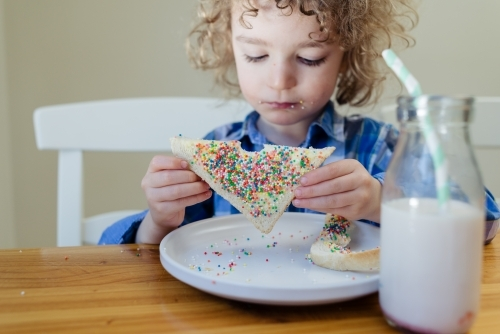 Portrait of a young boy with blond curly hair sitting at the table eating fairy bread