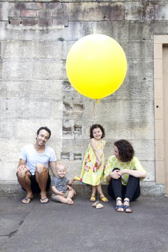 Portrait of a young family of four with a large yellow balloon
