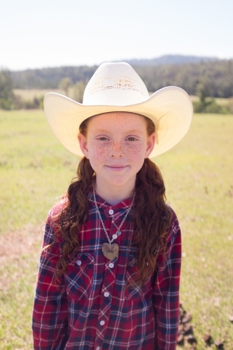 Portrait of a young girl in a cowboy hat and check shirt