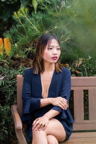 portrait of beautiful asian woman sitting on park bench