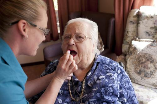 Portrait of elderly lady having lipstick applied by carer at aged care facility