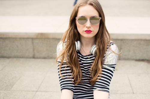 Portrait of fashionable young woman wearing sunglasses sitting down