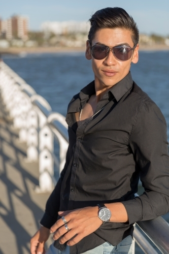 Portrait of trendy young man leaning on railing of pier with sunglasses