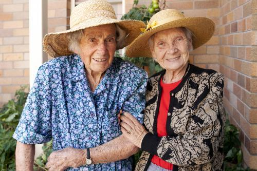 Portrait of two elderly ladies walking in the garden at an aged care facility