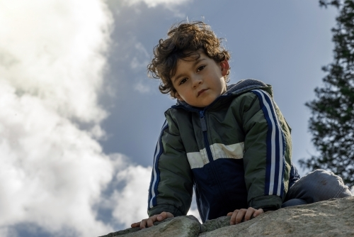 Portrait of young boy after climbing rock