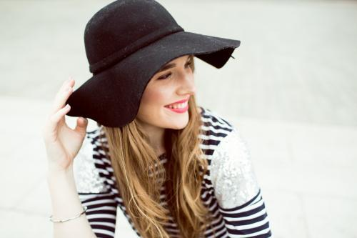 Portrait of young woman wearing a hat and looking over shoulder