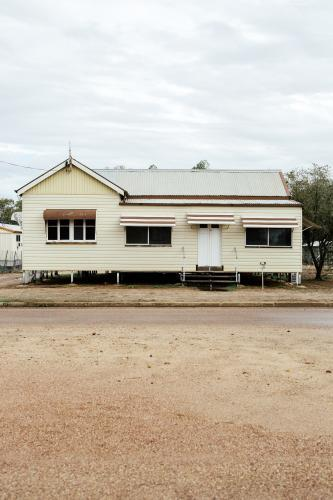 Portrait photo of cream coloured Queenslander House with brown trimming