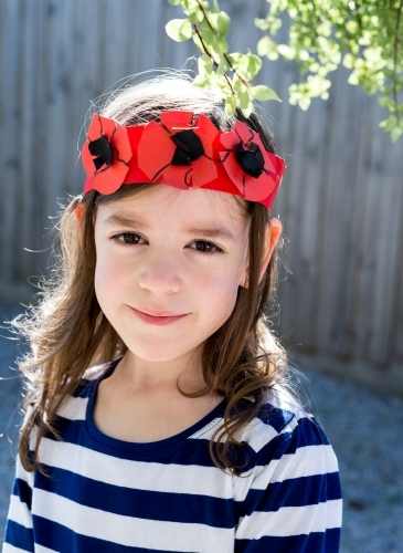 Portrait of a young girl smiling wearing a handmade crown of poppy flowers