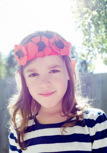 Portrait of a young girl wearing her hand made paper crown of poppy flowers