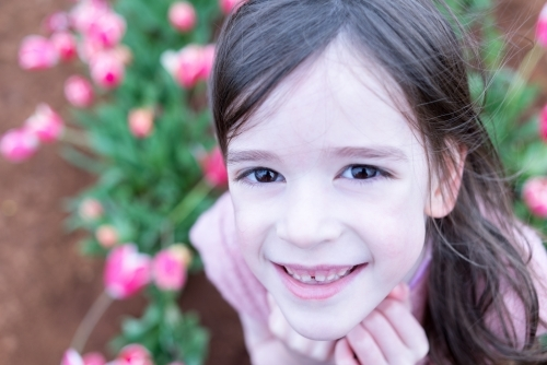 Portrait of a smiling young girl in a tulip garden looking up