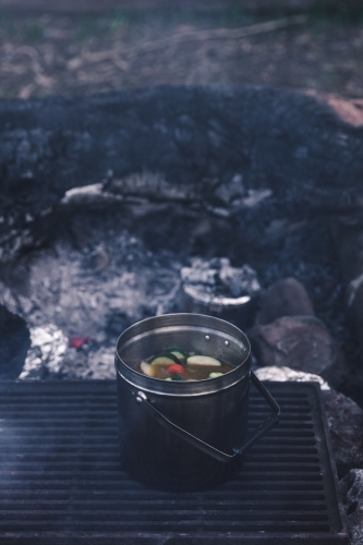 Pot of vegetable soup cooking on grill on campfire coals