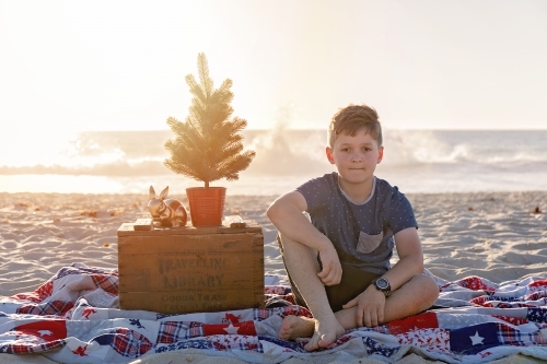 Pre Teen Boy Sitting In a Christmas Themed Setting At The Beach At Sunset
