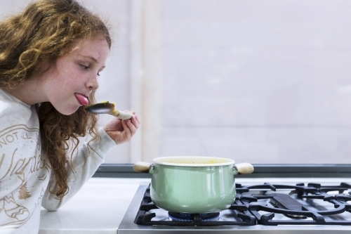 Preteen girl helping to cook over a saucepan on a stove in the kitchen