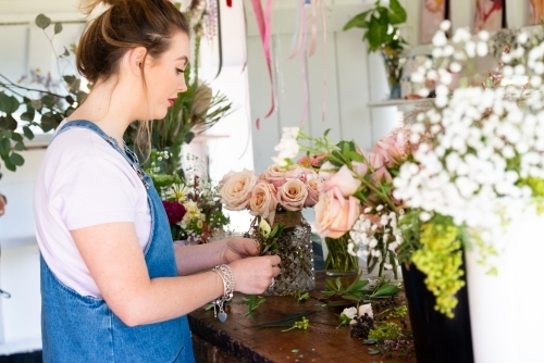Pretty young florist preparing wedding buttonholes at a work bench full of flowers