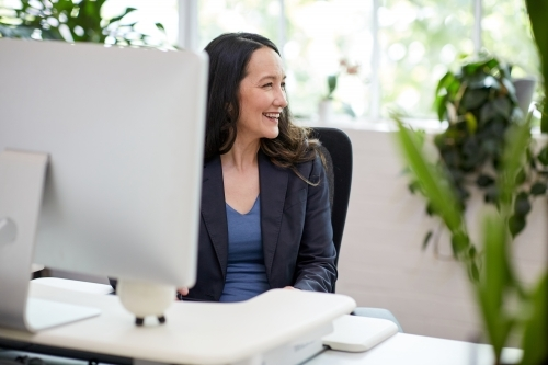 Professional business woman sitting at a computer in an office studio