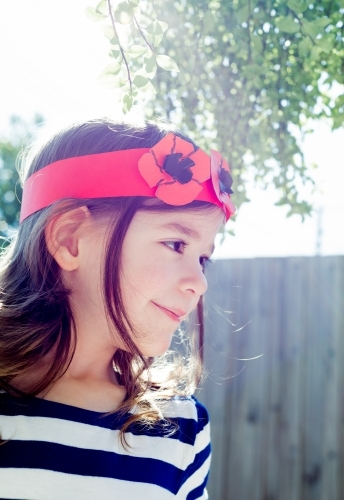 Profile of a young girl smiling wearing a hand made crown of poppy flowers