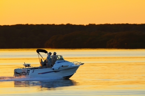 Two men in their 40's travelling fast in a fishing boat on a golden dawn in Pumicestone Passage, QLD