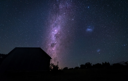 Purple milky way behind silhouetted house