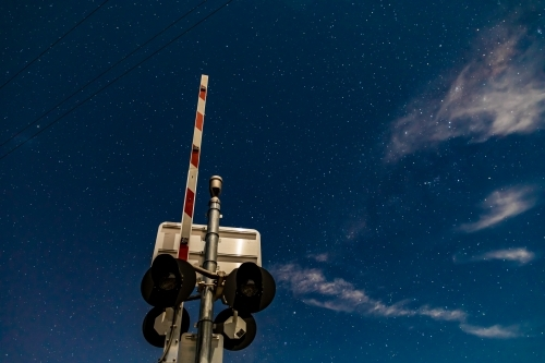 Rail crossing signals and boom barrier against the starry cloudy night sky