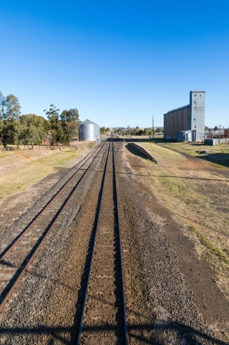 Railway lines leading up to industrial area with rail siding, platform and factory silos