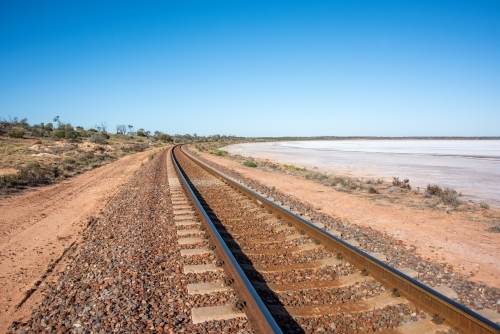 Railway track leading into the distance with salt lake next to it