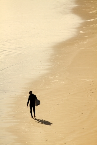 A man in his thirties walks along beach with surfboard.
