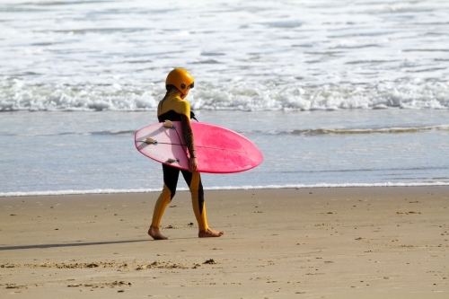 A young pre-teen girl walking along beach with surfboard under her arm.
