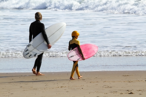 A dad and his young daughter walking along beach with surfboard under their arms.