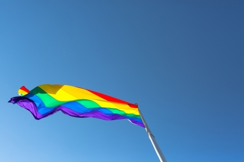 Rainbow flag against a blue sky