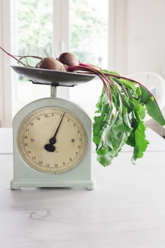 Raw beetroots on a set of vintage scales in a bright home